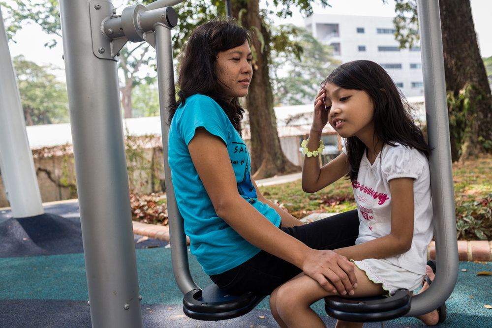 March 15, 2014 - Singapore. Tutik works full time (7days a week) looking after Izzati (7), in the morning they will go to the park together after lunch Tutik will take Izzati to the school bus which picks her up at her grandparents house. © Nicolas Axelrod / Ruom