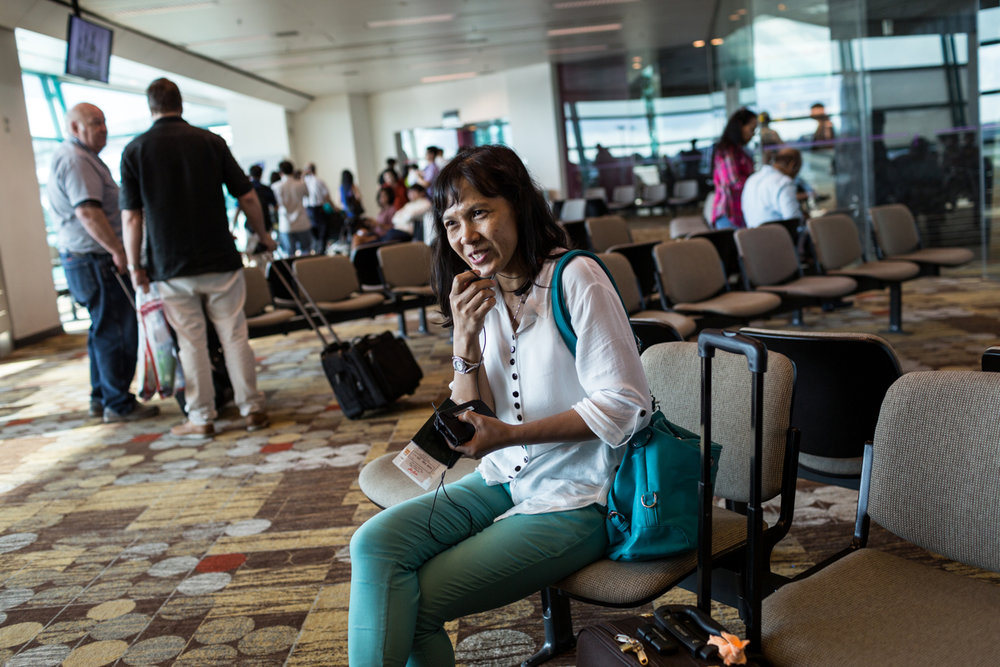 June 09, 2014 - Singapore. Tutik prepares to fly home. She finished her contract with her employer and waits to board her plane back to Semarang in Indonesia. © Nicolas Axelrod / Ruom