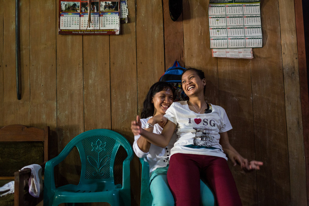 June 09, 2014 - Semarang, Indonesia. Tutik arrives home after working in Singapore for three years. Her daughter Ika is so happy she is home she doesn't leave her alone. © Nicolas Axelrod / Ruom