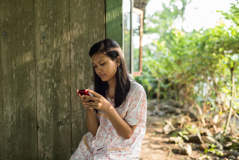 May 01, 2014 - Kendal, Indonesia. Tutik's daughter, Ika plays with her phone. During the three years her mother has been working in Singapore she has been able to see her once for 24hrs. © Nicolas Axelrod / Ruom