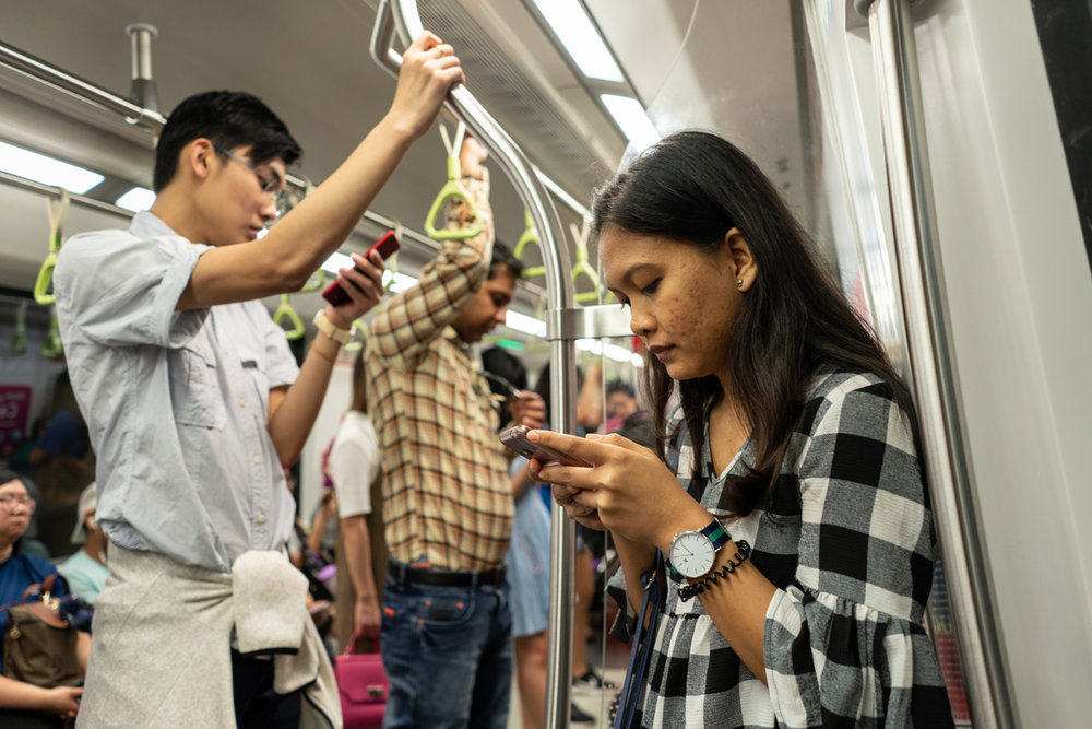 July 15, 2018 - Singapore. Eka, Tutik's eldest daughter on the MRT. Eka also works in Singapore as a domestic worker. © Nicolas Axelrod / Ruom