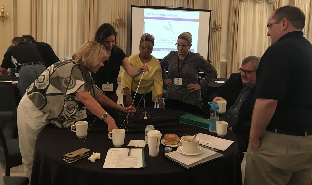 Coherence Lab Fellows engaging in a team-building exercise: The Marshmallow Challenge.