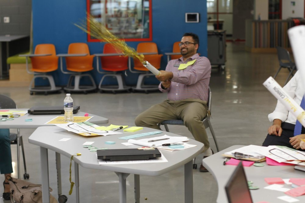 A teacher participating in the Creative Leadership Institute at Gwinnett County Public Schools shoots a confetti cannon. Confetti cannons are used as a tool for celebrating risk-taking.