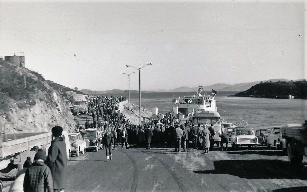 """Det er festdag på Sandstad, mars 1964. Masse mennesker, busser og biler og det er flagg som vaier. Det er åpningsdag for det nye fergesambandet mellom Sandstad og Storoddan i Hemne.Den nye """"Hitraferja"""" ligger flaggprydet i fergeleiet. Aunøya i bakgrunnen til høyre. (Foto Sten Strøm. Bildets eier Bjørn Strøm)"""