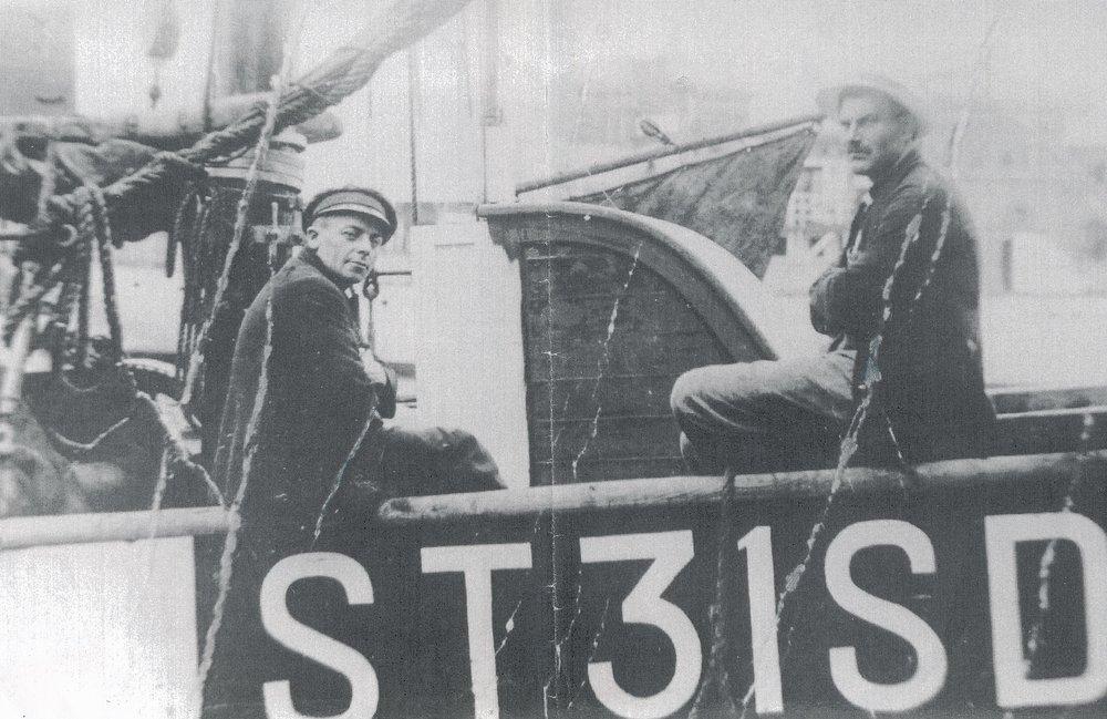 """ST 31 SD var motorkutter """"Veø"""" av Sandstad. Bildet er trolig tatt på 1920-tallet i Trondheim. Båt og mannskap gikk ned på Folla i forrykende uvær i 1929. Paul Strand (t.v.) og Laurits Skjevikdal sitter på rekka."""