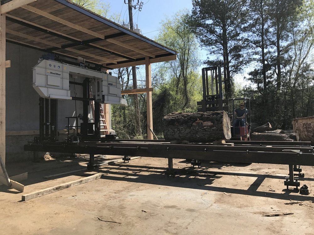 The log is delivered to Eutree's lumberyard, and loaded onto Wood-Mizer 1000 sawmill by forklift