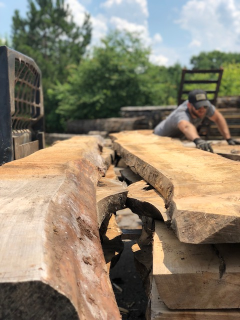Once air dried, the slab stack is lifted onto a bobcat to transport to the kilns for heat drying.
