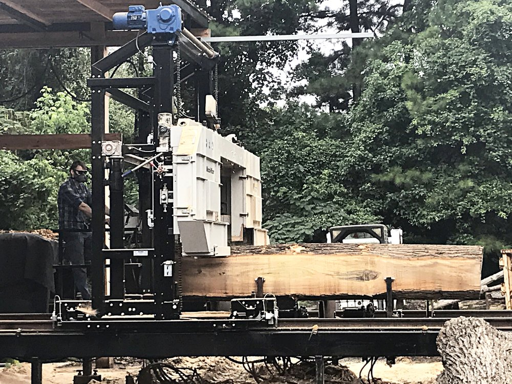 Eutree's Chief Sawyer, Sims, oversees the milling of each log into slabs on the Wood-Mizer 1000 sawmill.