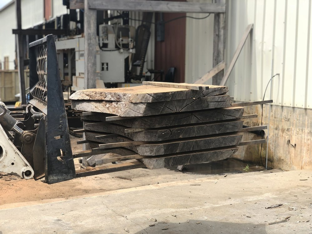 After the slabs are properly stacked and stickered, they are lifted into the warehouse by bobcat to begin the drying process.