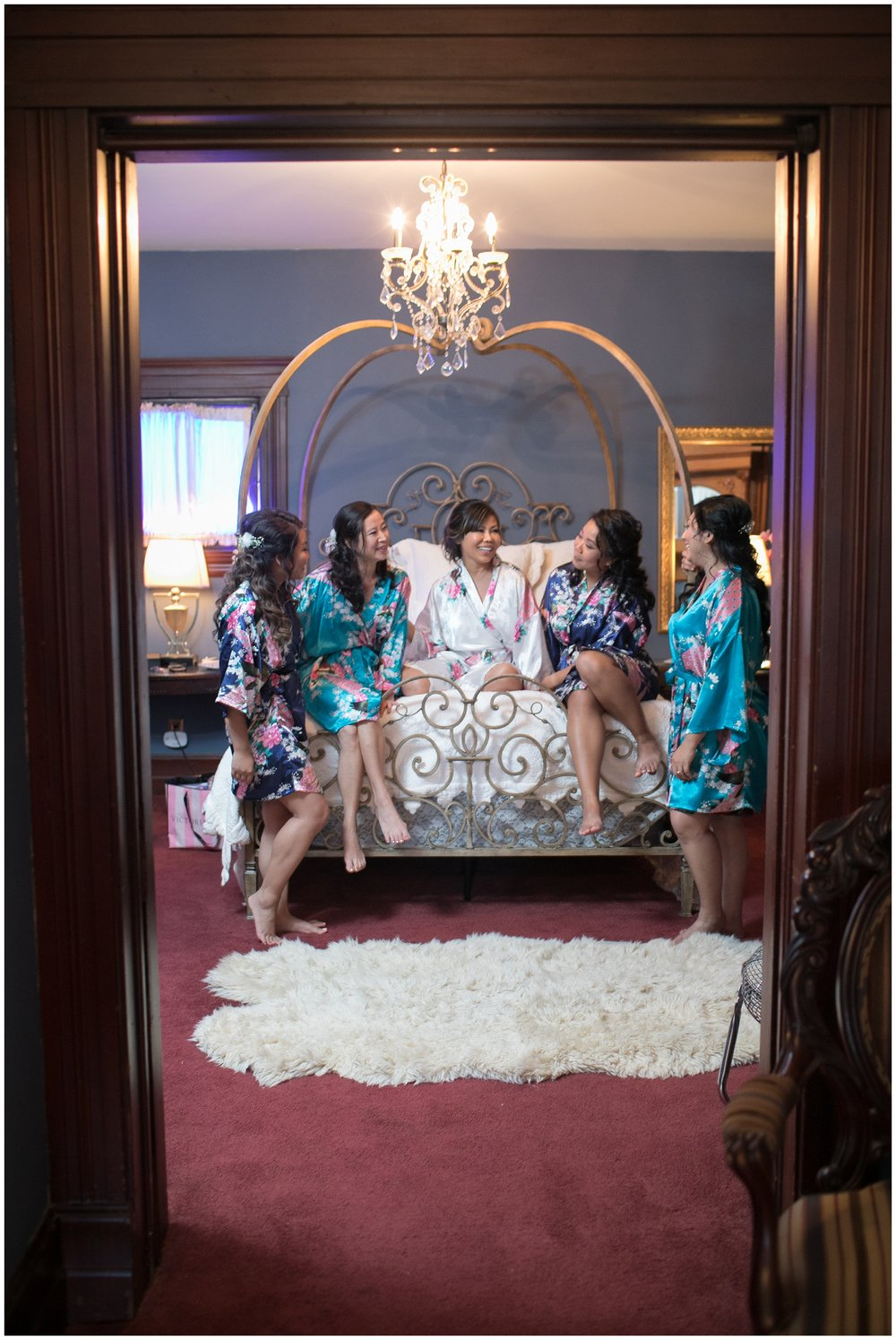 christmas house bridal party sitting on bed in bridal suite carrie vines
