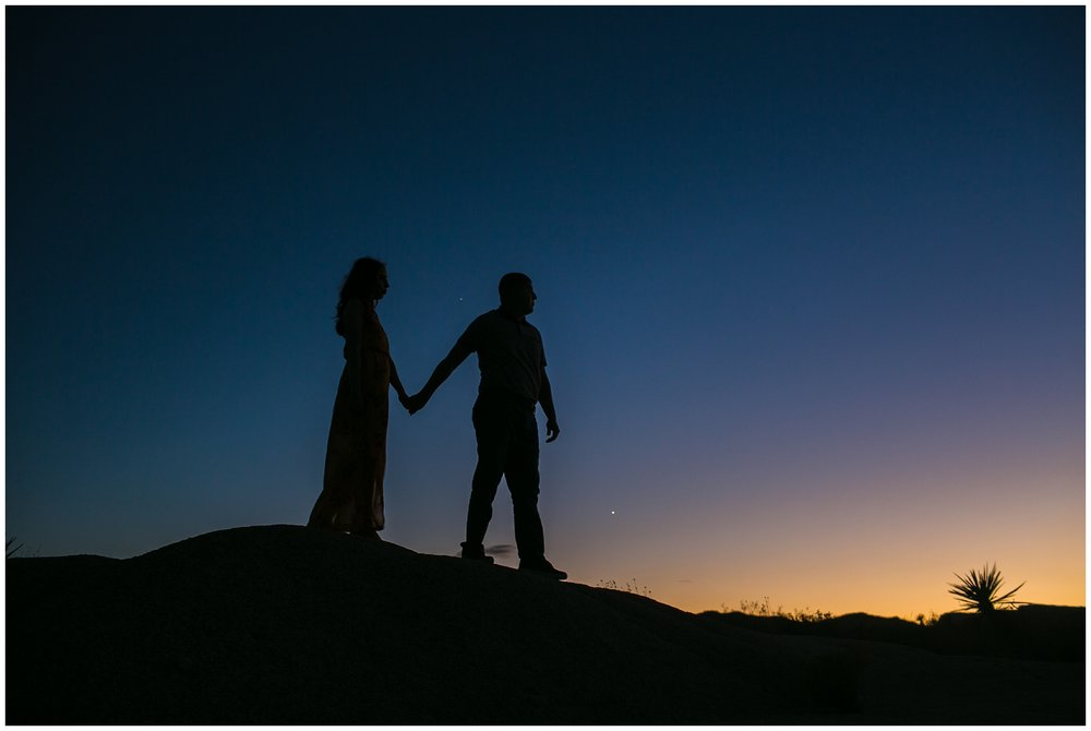 silhouette of couple walking in desert during sunset Joshua Tree Engagement Session, Desert Engagement Session, Palm Springs Wedding Photographer Carrie Vines