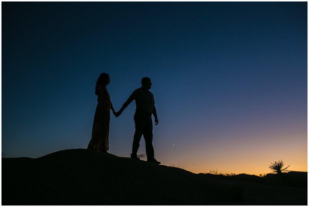 silhouette of couple walking in desert during sunset Joshua Tree Engagement Session, Desert Engagement Session, Palm Springs Wedding Photographer Carrie Vines