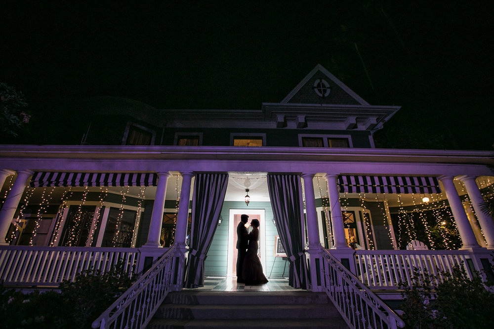 christmas house inn and gardens wedding carrie vines photography bride and groom backlit on front porch of victorian historic home romantic wedding portrait