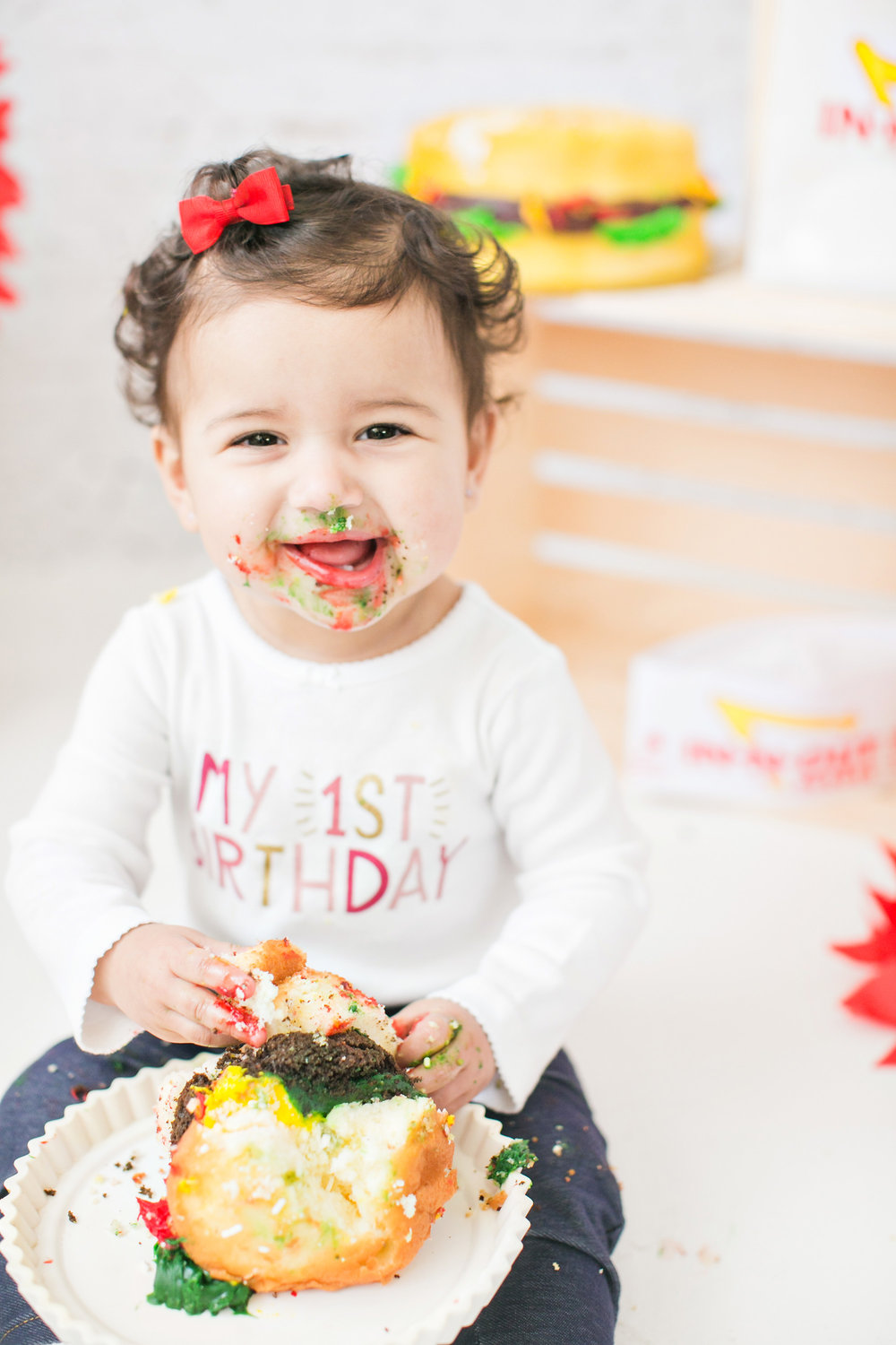 happy smiling one year girl enjoying her in-n-out cake smash session, Redlands baby photography studio carrie vines photography