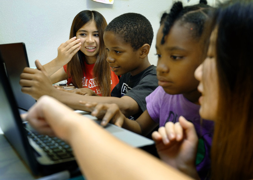 Open Sesame Coding for Kids project co-founder Milan Narula, left, helps Thomas House resident Jeremiah, 10, as UCI student volunteer Yoonjo Kim, far right, works with 9-year-old Dymond during a computer coding class at the temporary shelter for homeless families in Garden Grove, on Friday, Nov. 2, 2018. (Photo by Michael Fernandez, Orange County Register Contributing Photographer)