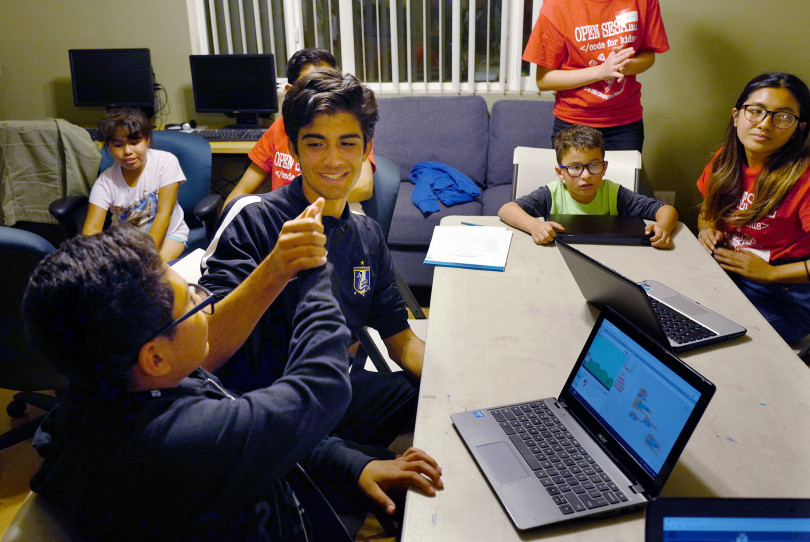 Chirag Singh, a volunteer from Troy High School with the Open Sesame Coding for Kids project, gives a high five to a student during a computer coding class at Thomas House in Garden Grove, a temporary shelter for homeless families on Friday, Nov. 2, 2018. (Photo by Michael Fernandez, Orange County Register Contributing Photographer)