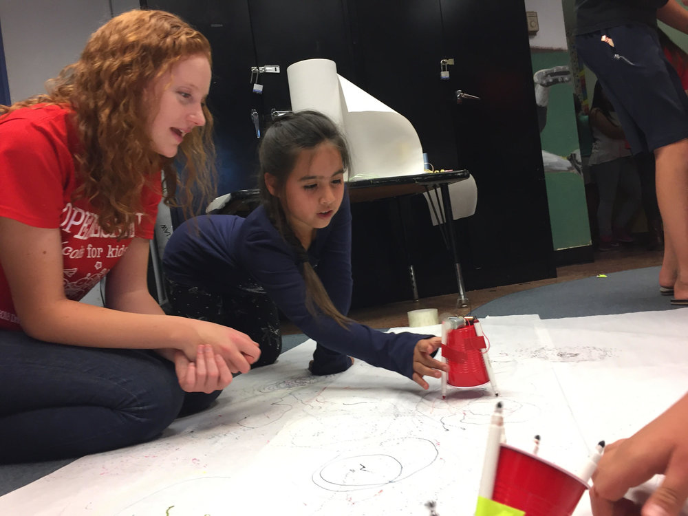 Katherine McPhie, left, co-founder of Open Sesame Coding for Kids, helps an Orange County Rescue Mission resident construct a motorized ArtBot during a computer coding class at the temporary shelter for homeless families in Tustin on Monday, November 12, 2018.