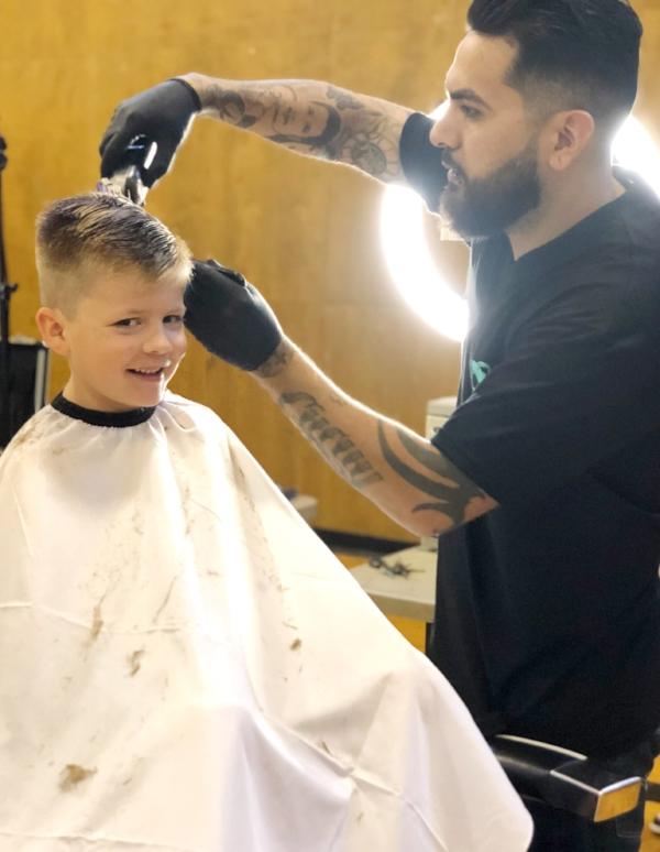 Joey, 7, gets his haircut by Sal Mireles of Legendary Barbershop