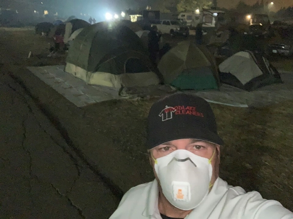 Dean Machado in front of camps set up for fire victims