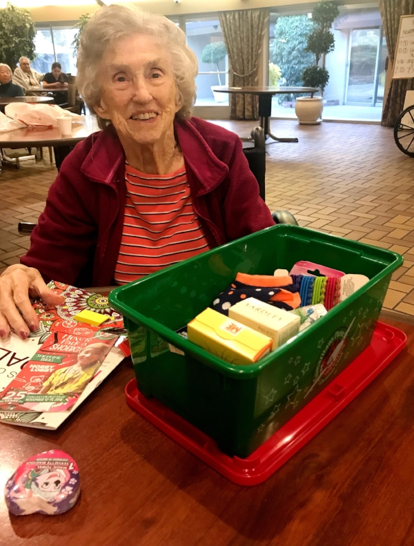 Violette puts gifts for a young girl in a box as part of Operation Christmas Child