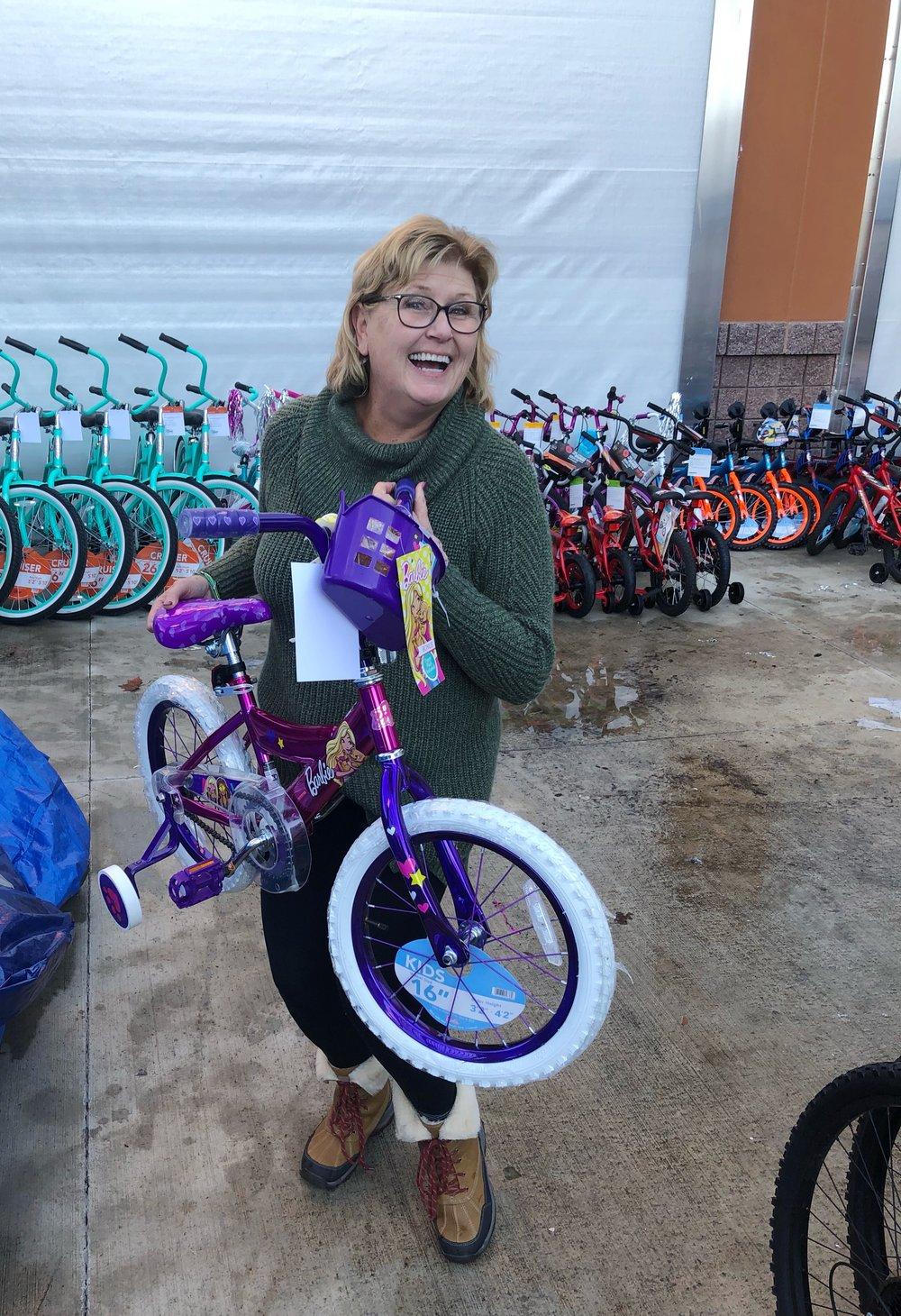 Sue Camper, Rotary member, loading a little girl's bike
