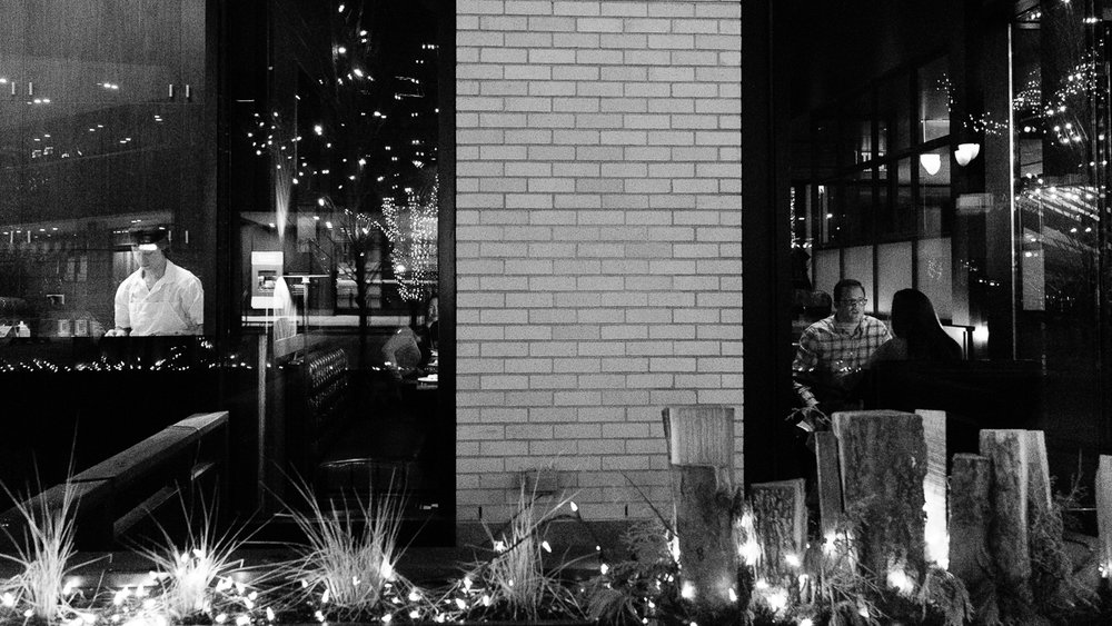 Day 22 - 365 Day B&W Photo Challenge - Went for a photo walk with the night photography group this evening and decided to do some street photography.  Here's a scene eating dinner at a restaurant along 16th Street Mall. - Fuji XT2, XF23mm f/2, Acros Film Simulation