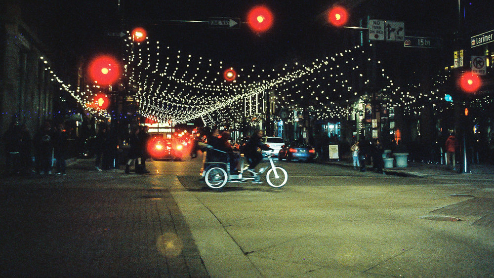 Pedicab crosses along 15th Street near Larimer Square