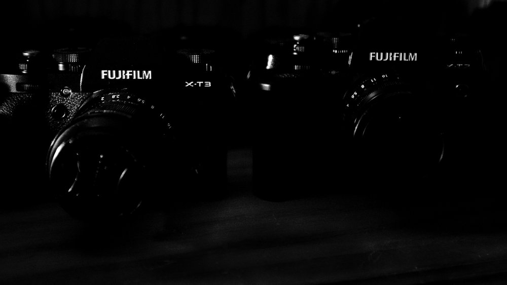 Day 60 - 365 Day B&W Photo Challenge - Small light in my office highlighting the logos of my Fuji XT-3 and XT2 on my camera shelf. - Fuji X100F, Acros R Film Simulation