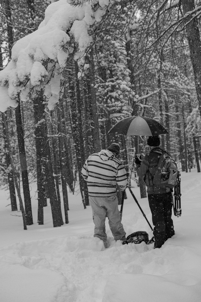 Ryan setting up a shot as Chase covers his camera during a snow storm in Rocky Mountain National Park
