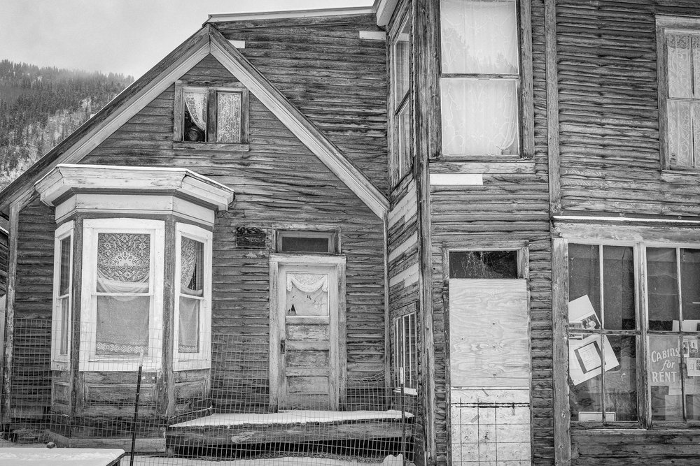 Day 142- 365 Day B&W Photo Challenge - Do you see someone looking at you?  It freaked me out when I first saw it. A face pearing out of this abandoned building in St. Elmo ghost town near Buena Vista, Colorado.. - Fuji X-T3, XF 35mm f/2, Acros R Film Simulation