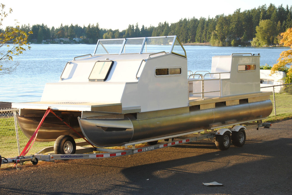 EcoCruiser Pontoon - EcoCruiser is a new style of pontoon/catamaran trailerable cruiser. She sleeps 4 in two low profile cabins and can be towed by a mid-sized SUV, like a Ford Explorer. The main cabin has standing headroom, a private head w/ door, galley, and extra-long full-sized island berth. Courtesy of Word Boats.