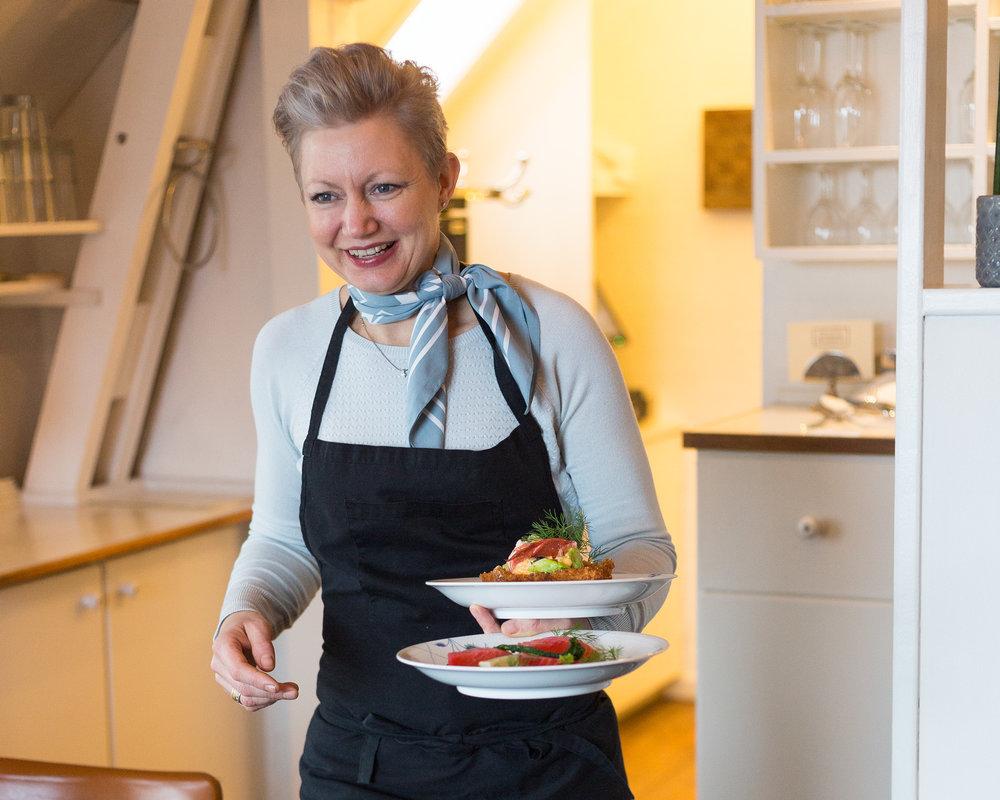 """Berit Bjørnestad - Ejer Berit Bjørnestad. Berit er uddannet kok, med mere end 20 år på bagen. Berit er født og opvokset i Gilleleje. Hun har i en årrække drevet flere restaurationer i Frederikssunds området, men er nu vendt tilbage til fødebyen. Med sig bringer hun, stolthed, godt håndværk, et skarpt øje for kvalitet, og et drive for at skabe den ultimativ oplevelse for vores gæster. Berit sammensætter vores aftenmenu, efter sæsonens fisk og grønt. Igen er intet tilfældigt, men derimod, valgt med omhu. Hvilket også er derfor vi ikke kan """"bikse noget sammen""""."""