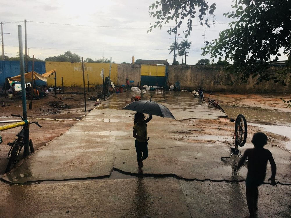 Child playing in the rain in Warao Indigenous community shelter in Boa Vista. Members of the Warao Indigenous Peoples were displaced early by Venezuela's economic crisis, and have been in this shelter since late 2016.