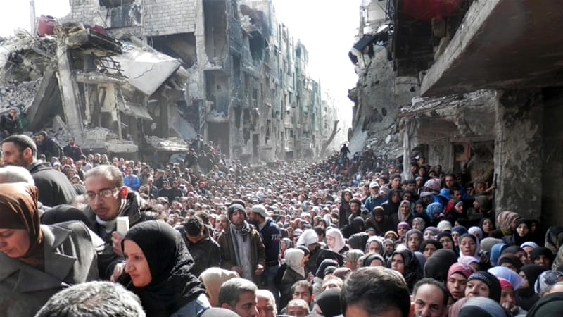 Residents of Yarmouk camp on the outskirts of Damascus queuing to receive food supplies when the camp was besieged. Syria 2014. Photo: UNRWA via AP