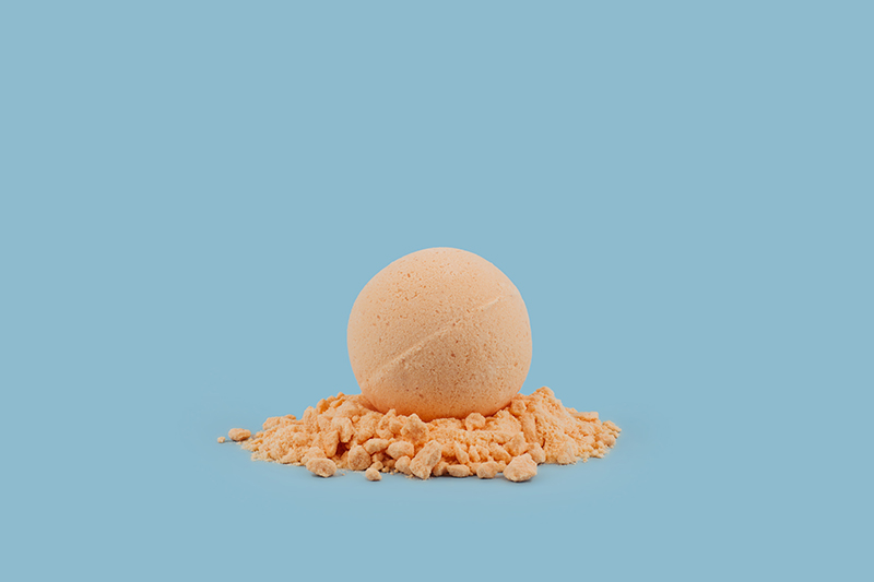 Orange Love CBD Kush Queen bath bomb sitting on top of bath bomb crumbles with blue background.