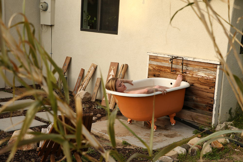 Model pictured relaxing in outdoor tub using Kush Queen bath bomb.