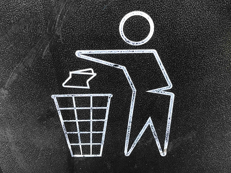 "Hand drawn ""Trash"" image featuring figurine tossing paper into wastebasket."
