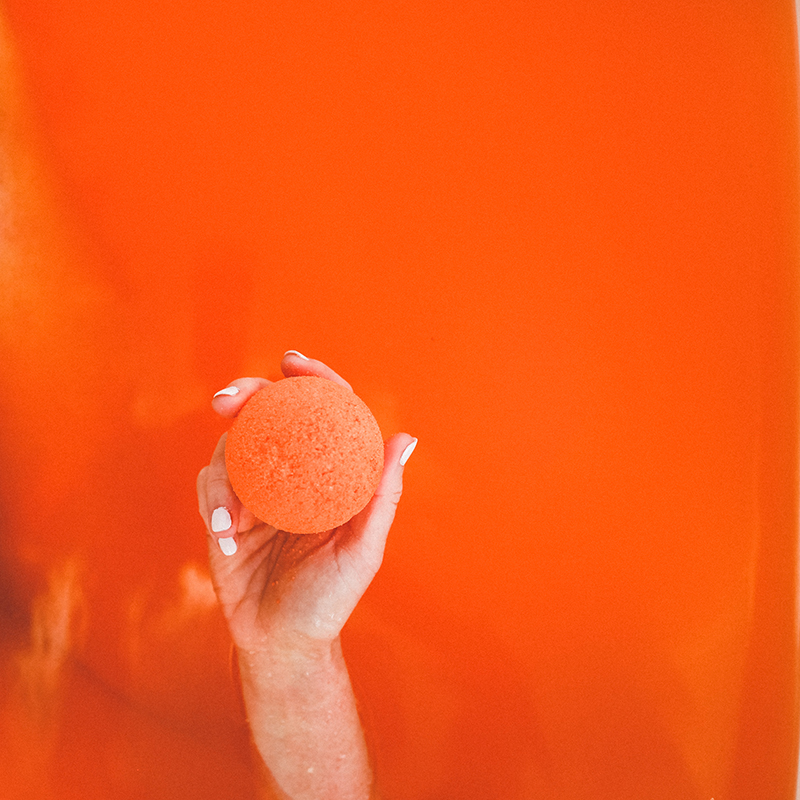 Model holds orange Citrus CBD bath bomb out of orange bath tub water.