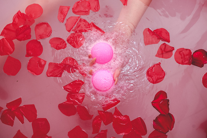 Model holds two pink Awaken CBD Kush Queen bath bombs in tub of water with floating rose petals.