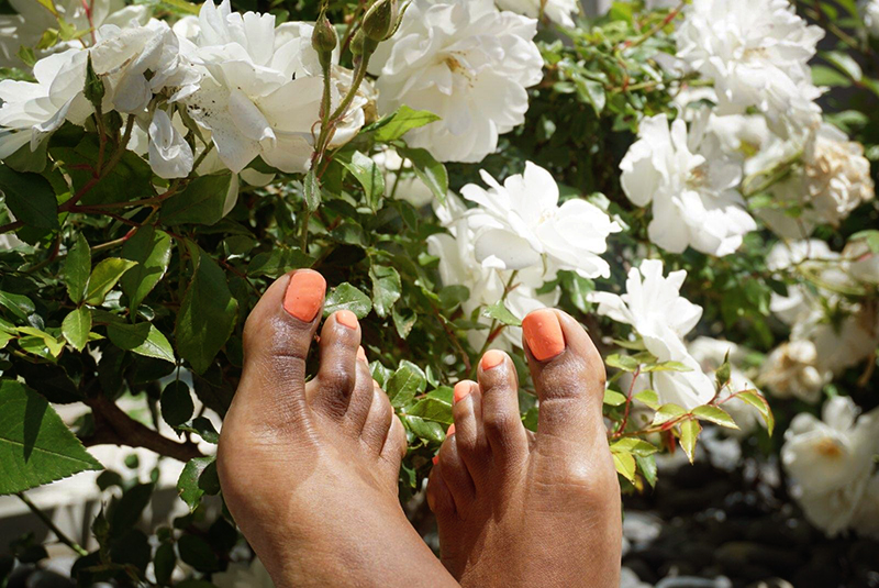 Pedicured toes on model with white flowers in garden in background.