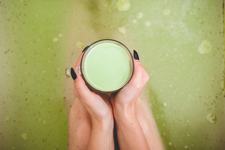 Model is holding glass of green tea in clear mug while sitting in bathtub with dissolved Match Tea 25mg bath bomb by Kush Queen.