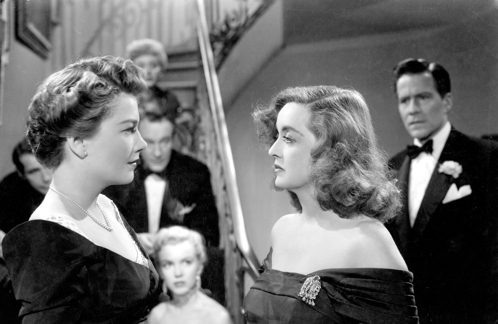 Anne Baxter (left foreground) and Bette Davis (right foreground) in  All About Eve , with Celeste Holm (center top), George Sanders (center middle), and  Marilyn Monroe  (center bottom) looking on