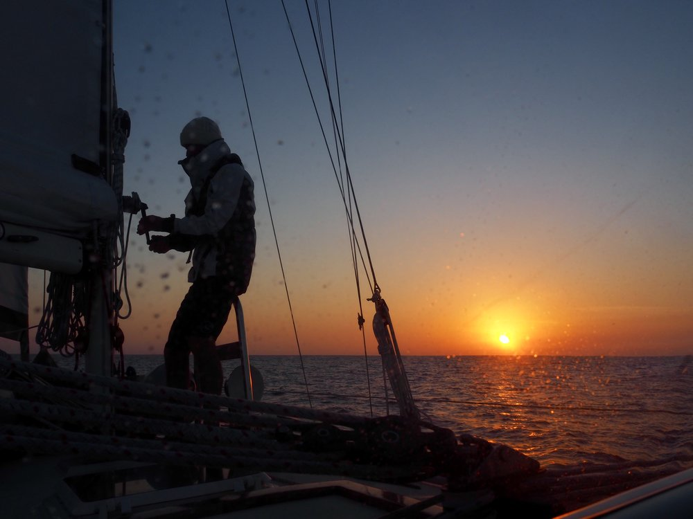 Colin, reefing the main at sunset for an easier overnight passage from Dana Point to San Diego.