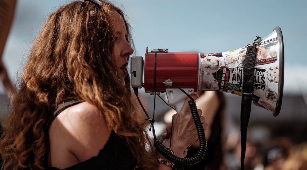 Woman holding bullhorn at demonstration.