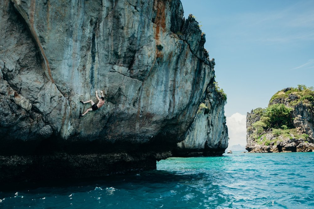 "Climbers scale cliffs without ropes above the sea, known as ""deep water soloing"" in Tonsai Bay, Thailand. March 2017."
