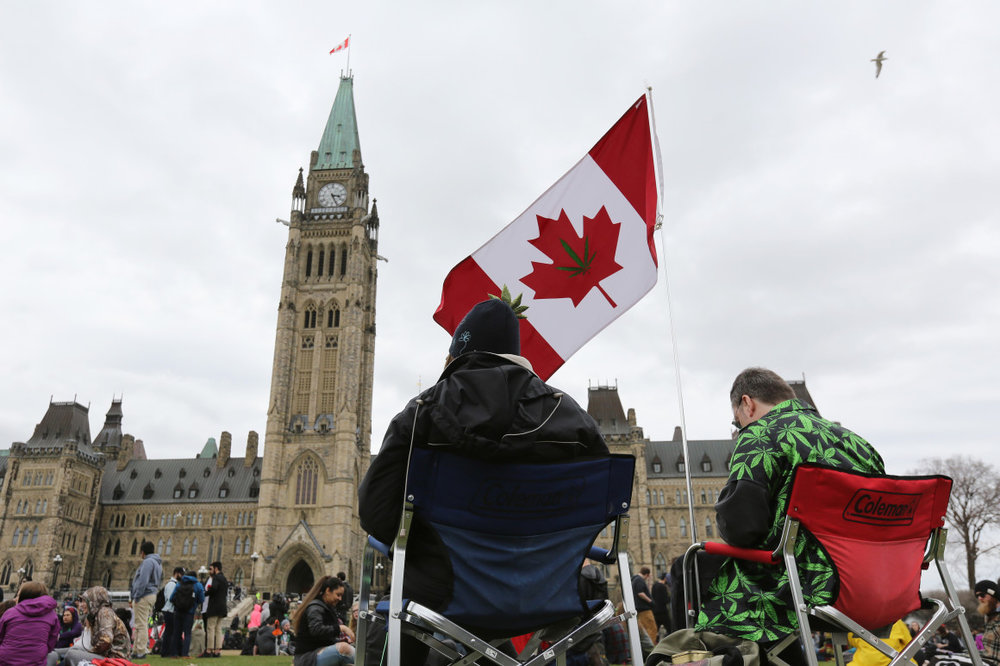 People sit on Parliament Hill waiting for the clock to hit 4:20 p.m. on April 20, 2017, in Ottawa. | Lars Hagberg/AFP/Getty Images