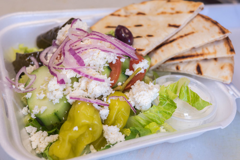 MEDITERRANEAN SALAD  - Lettuce, tomatoes, cucumbers, Kalamata olives, dolmades, pepperoncini, red onions, feta cheese, homemade Tzatziki sauce, and a grilled pita.