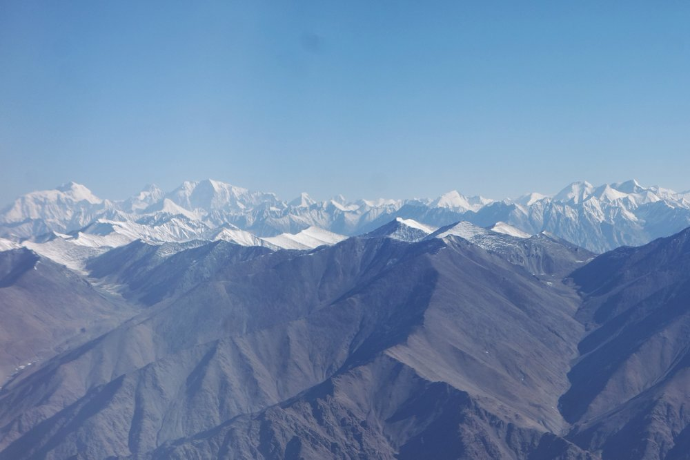The Spires of the mighty Karakorams appearing beyond the Ladakh Range. In this case the Saser Massif.