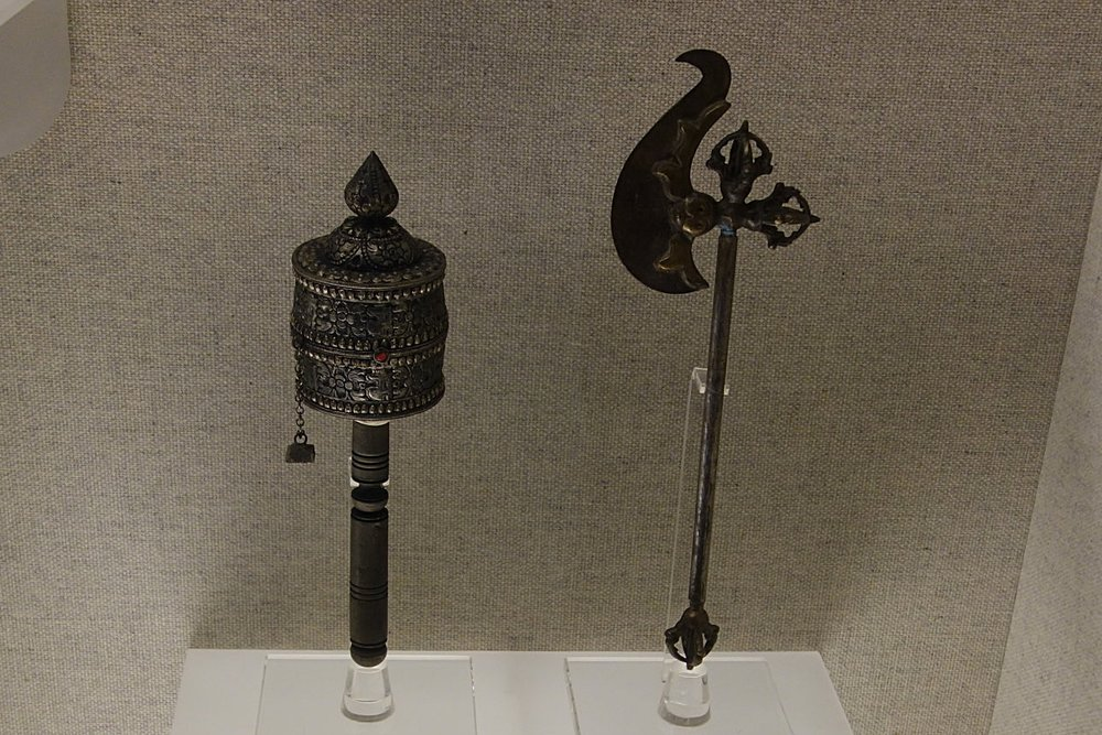 Left : Silver Prayer Wheel with a hammered Motif Right : Brass Vajra Axe