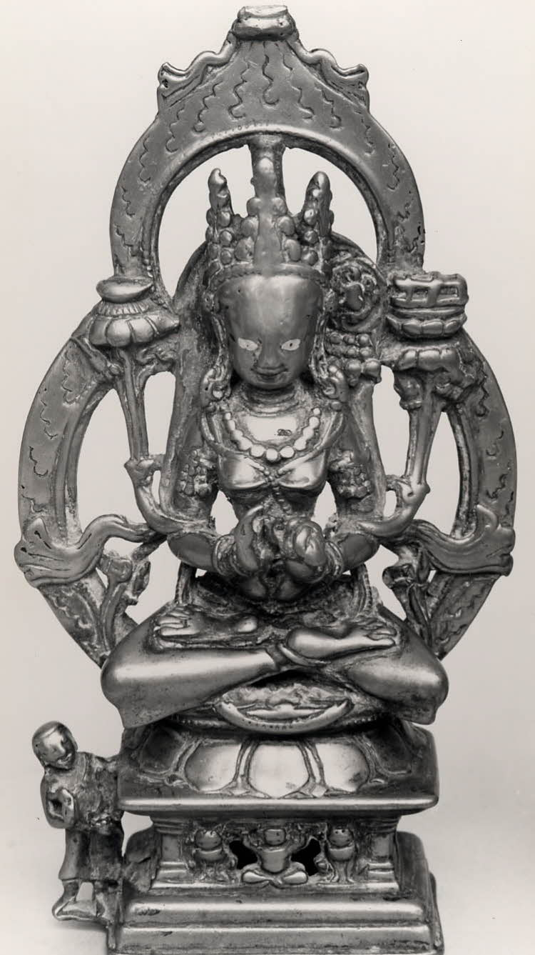 A bronze figure of Prajñāparamitā, holding a lotus and a book seated on a lion throne.